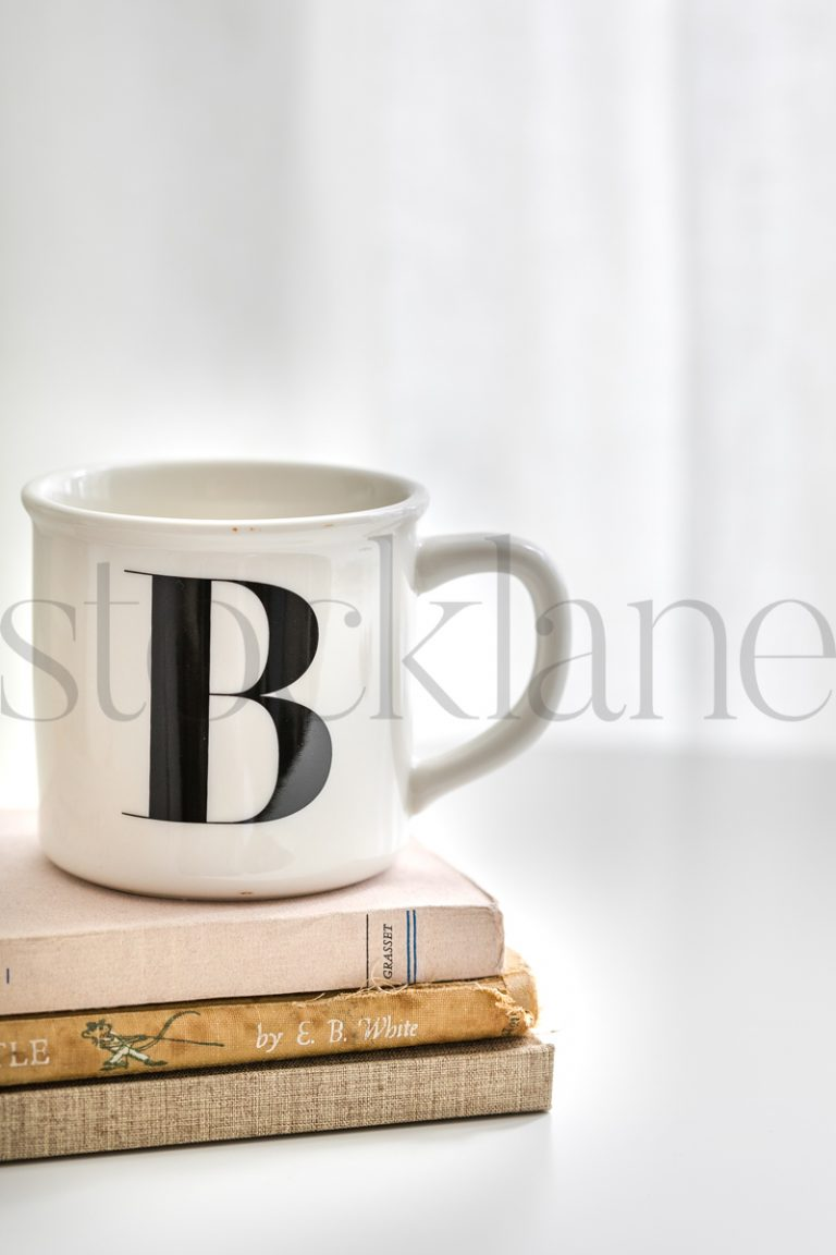 Vertical stock photo of a coffee cup and books