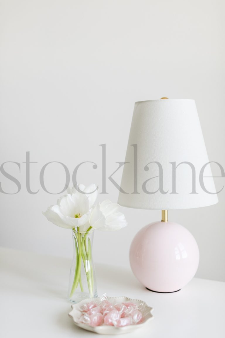 Vertical stock photo of flowers in vase and lamp