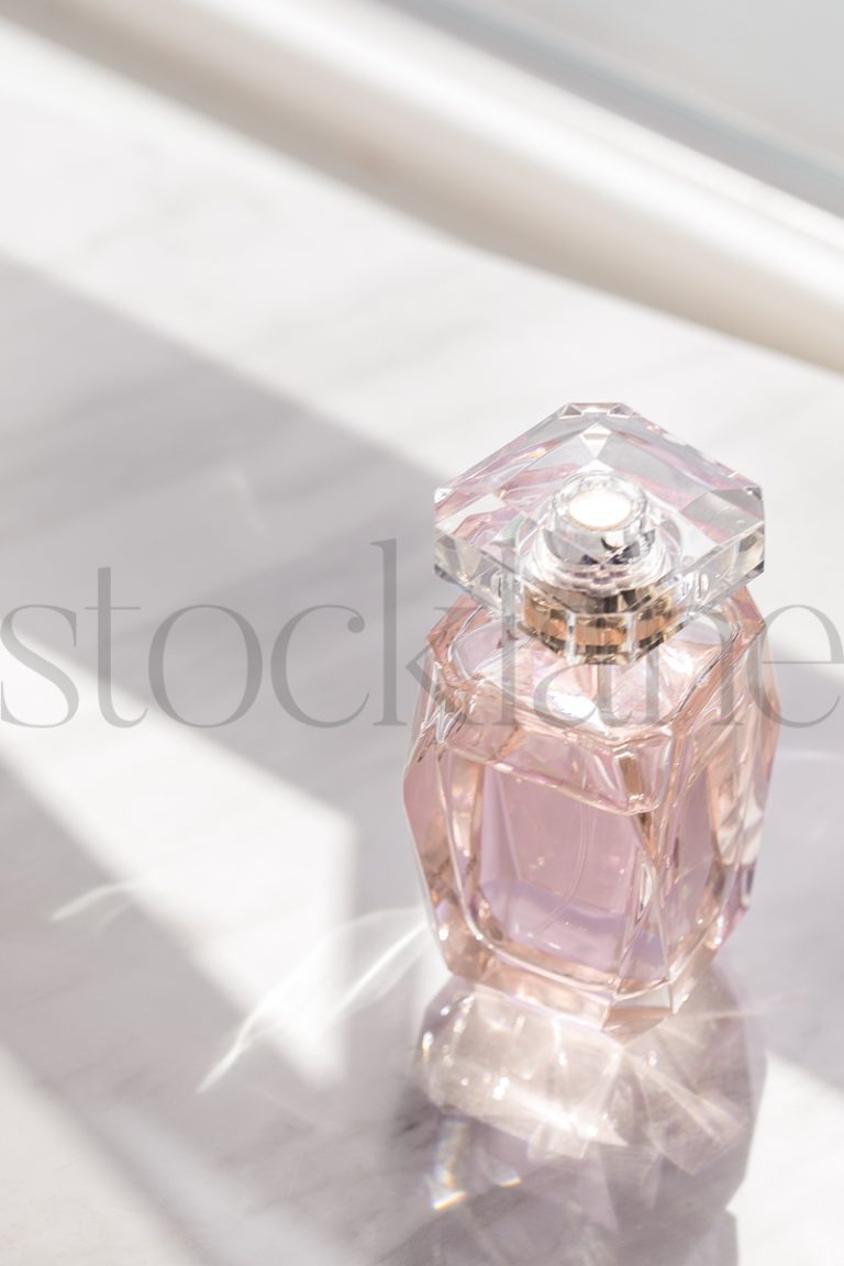 Vertical stock photo of pink perfume bottle