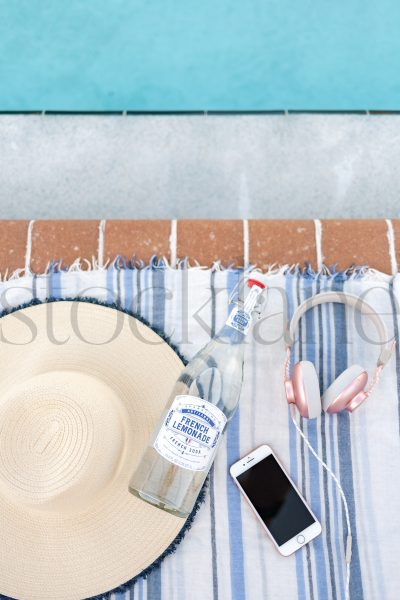 Vertical Stock photo of beach towel, hat, bottle and phone