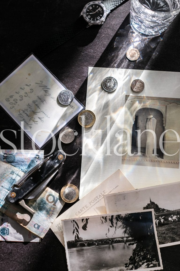 Vertical stock photo of coins, notes, and pocket knife