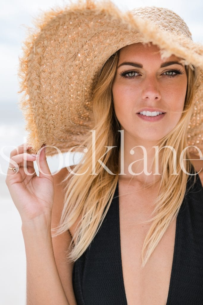 Vertical stock photo of woman at the beach with large hat