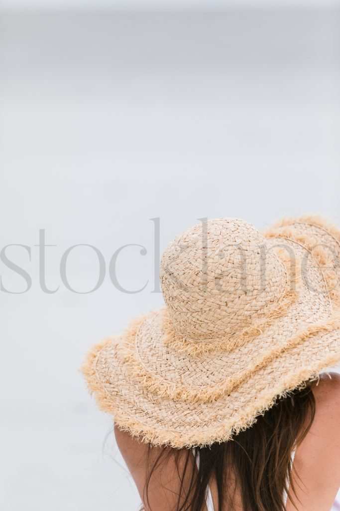 Vertical sock photo of woman at the beach with large hat