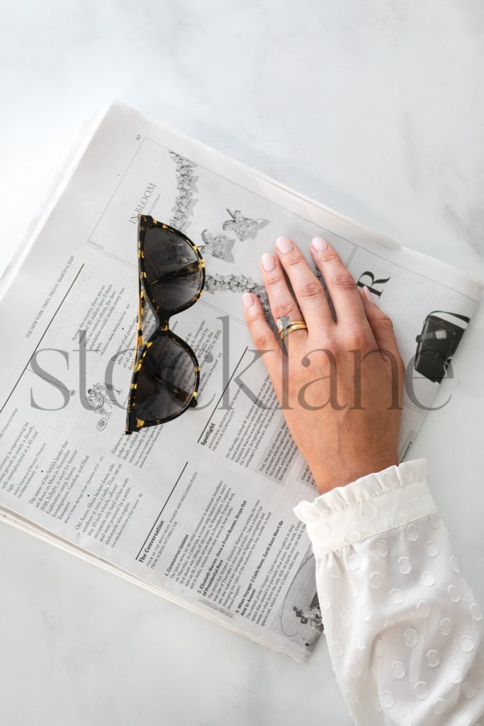 Vertical stock photo of a woman's hand on newspaper