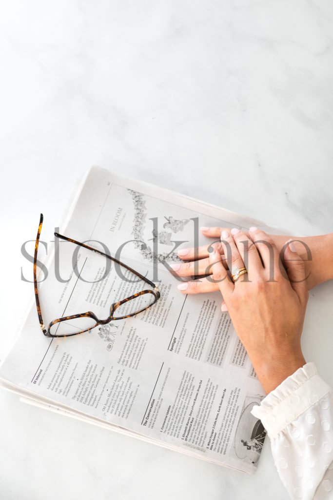 Vertical stock photo of woman's hands on newspaper