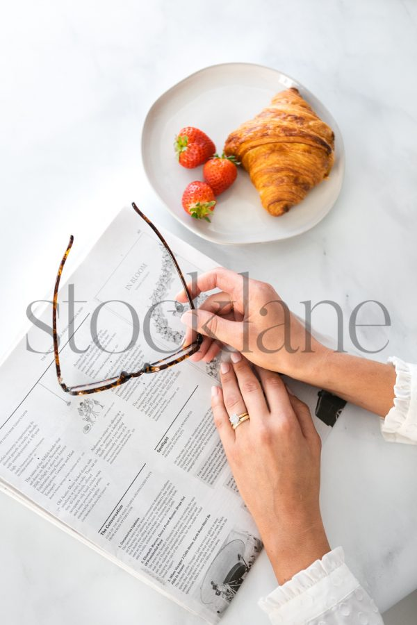 Vertical stock photo of woman's hands and newspaper