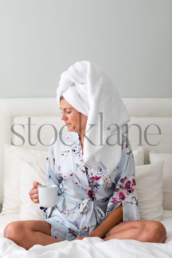 Vertical stock photo of woman in bathrobe having coffee