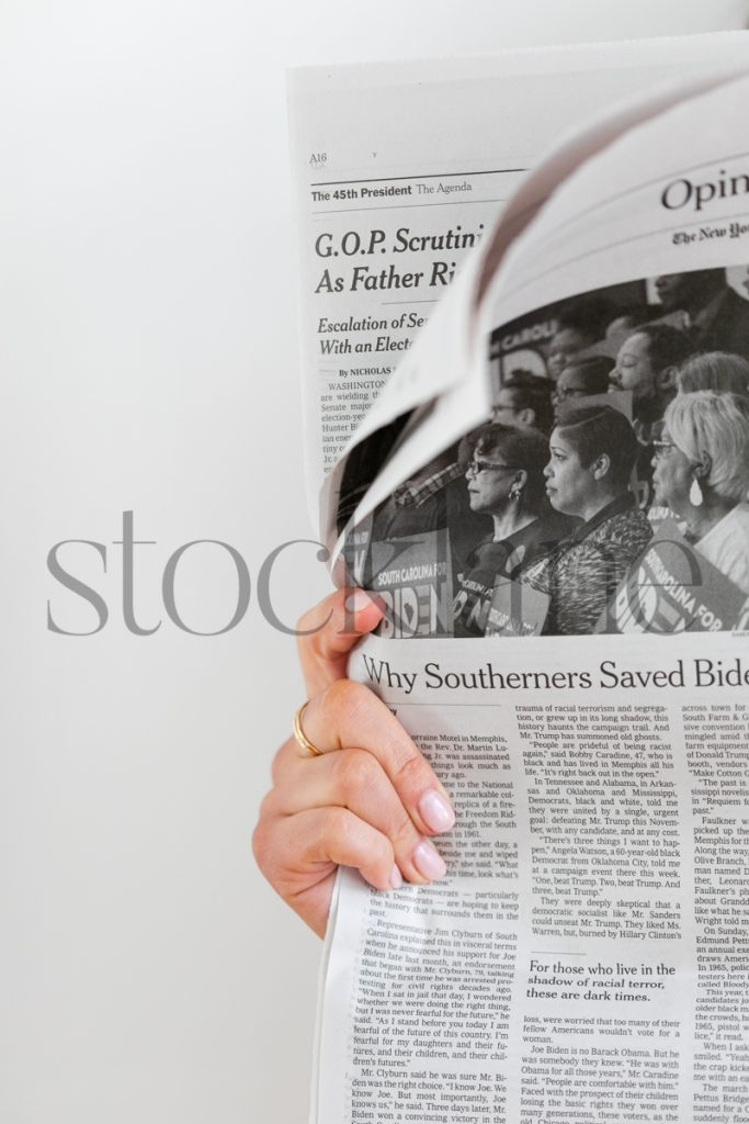 Vertical stock photo of hand holding newspaper