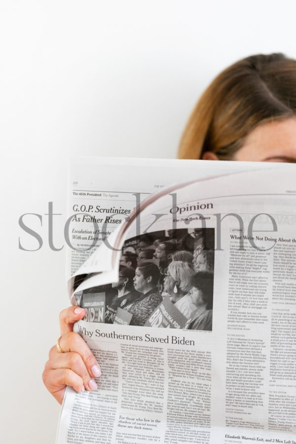 Vertical stock photo of woman reading the newspaper
