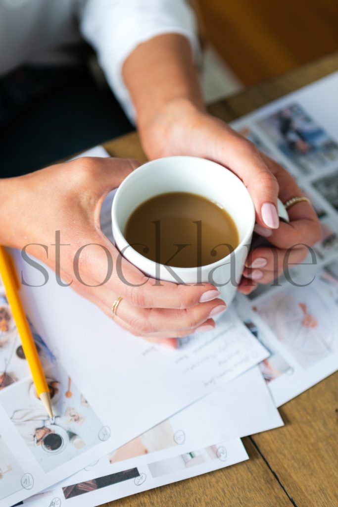 Vertical stock photo of hands holding coffee cup