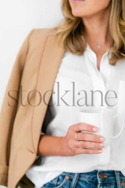 Vertical stock photo of woman holding coffee cup