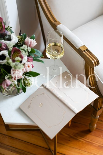 Vertical stock photo of wine glass and book