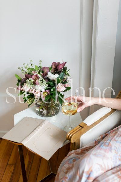 Vertical stock photo of woman with book and wine