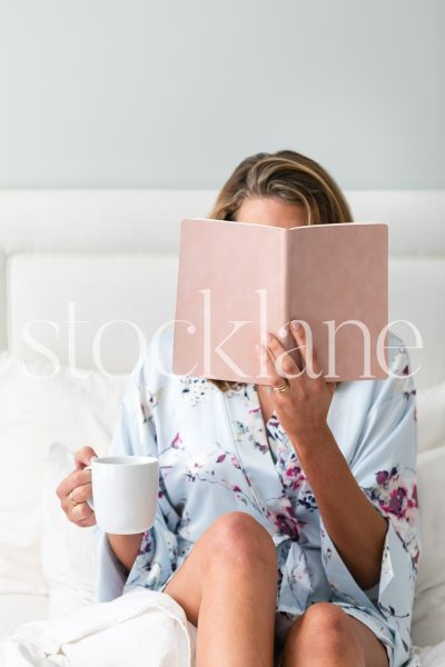 Vertical stock photo of woman reading in bed