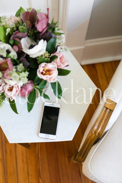 Vertical stock photo of side table with flowers and phone