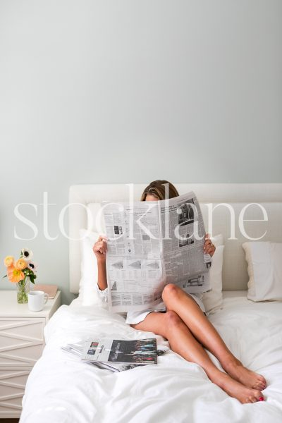 Vertical stock photo of woman reading newspaper in bed