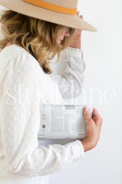 Vertical stock photo of woman holding a newspaper