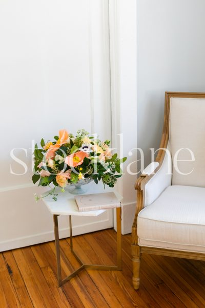 Vertical stock photo of reading chair and side table with flowers