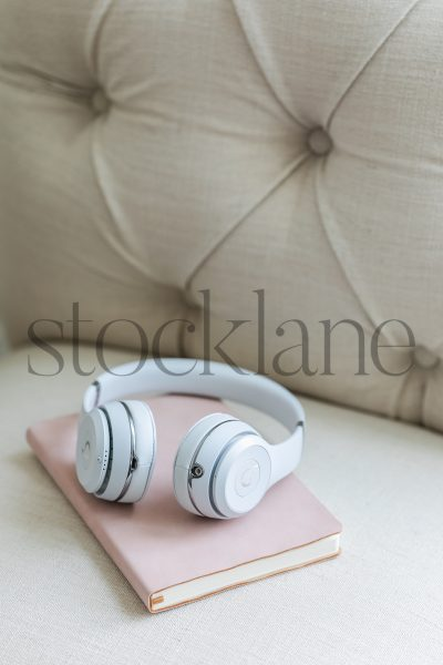Vertical stock photo of a pink notebook and white headphones on a chair.