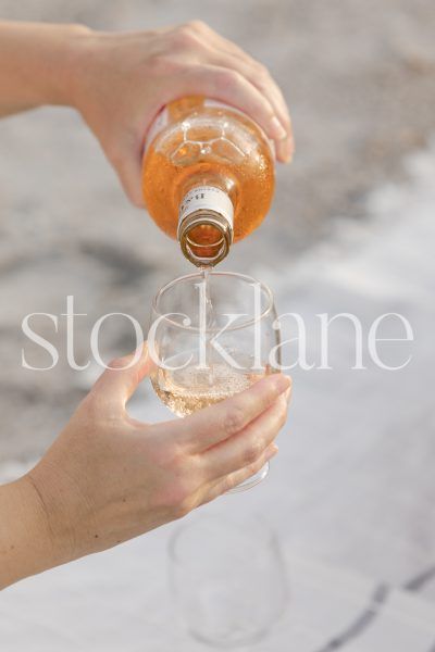 Vertical stock photo of woman pouring rose wine.