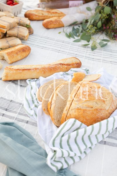 Vertical stock photo of bread at beach picnic.