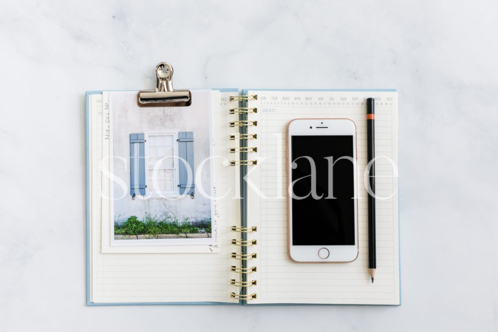 Horizontal stock photo of a notebook and a phone on a marble surface