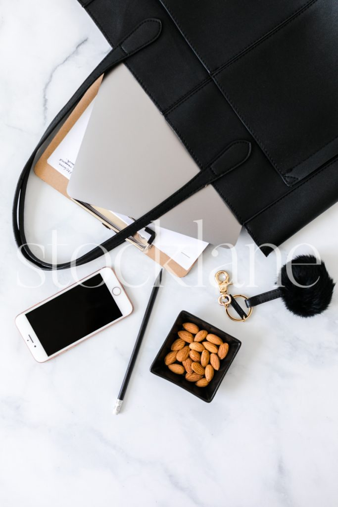 Vertical stock photo of handbag with computer and notepad.