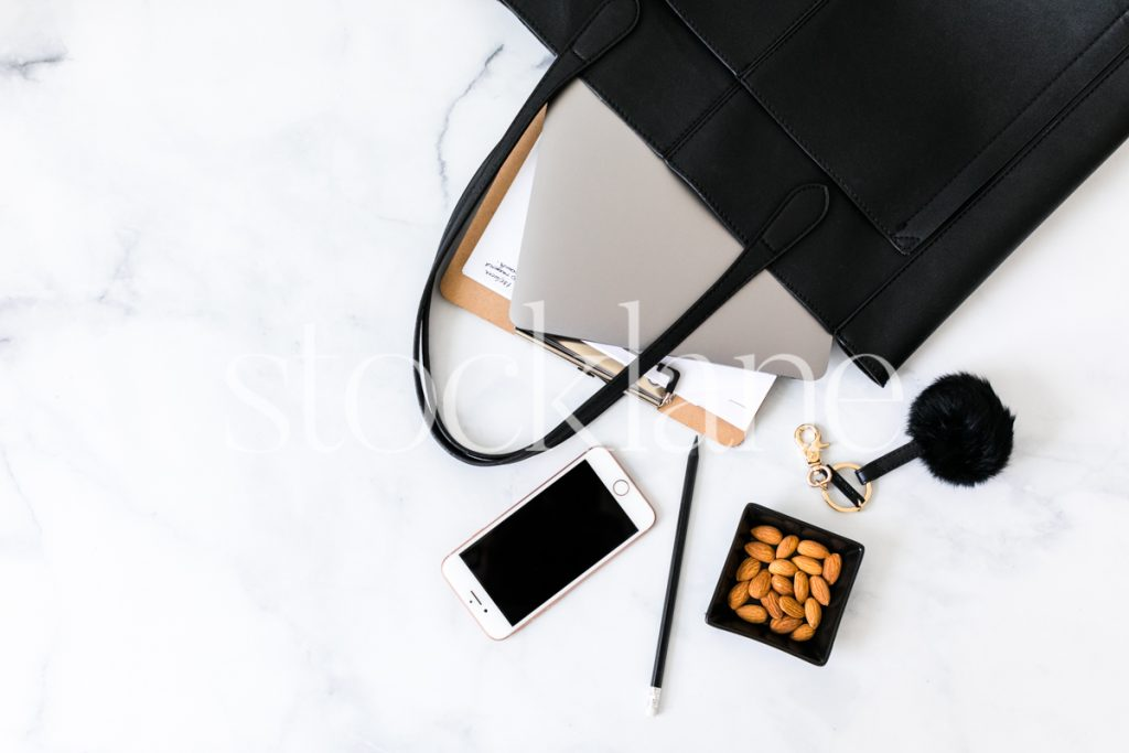 Horizontal stock photo of handbag with computer and notepad.