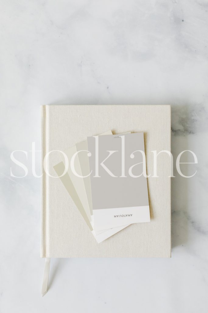 Vertical stock photo of notebook and paint color cards.
