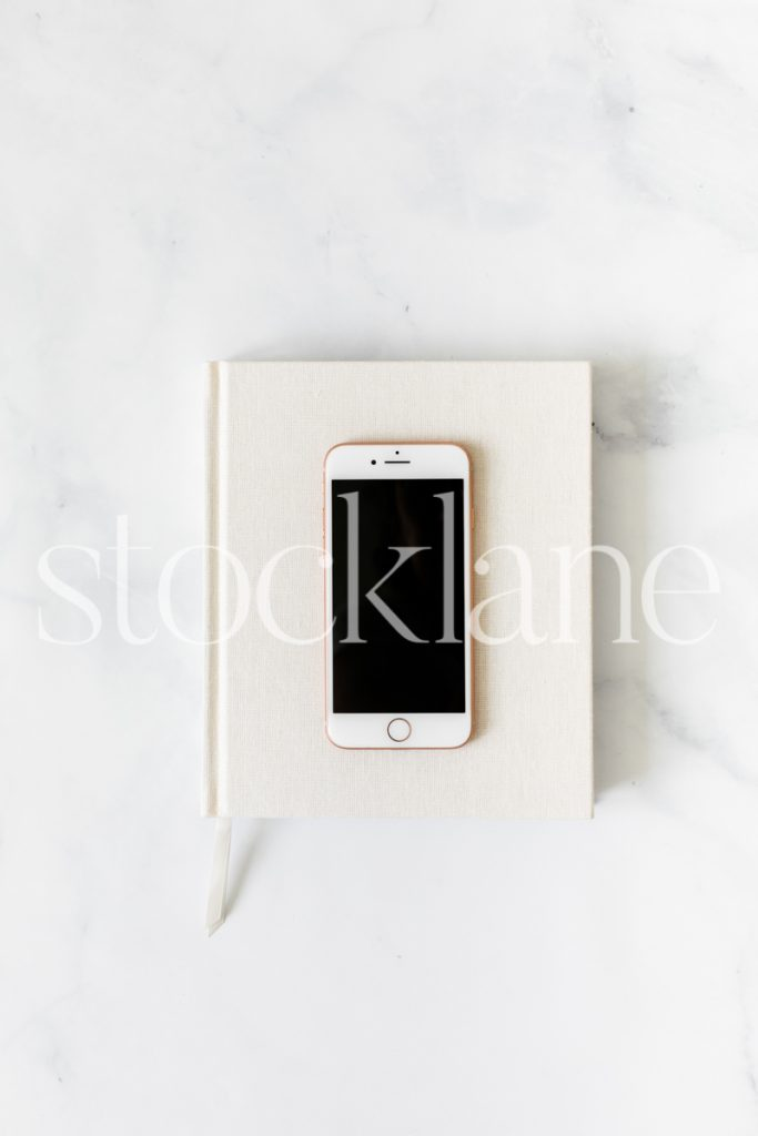 Vertical stock photo of a notebook and a phone