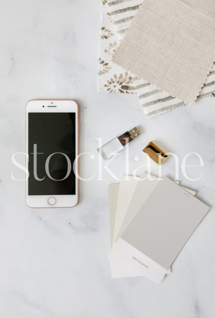 Vertical stock photo of a phone and designer fabric and paint samples.