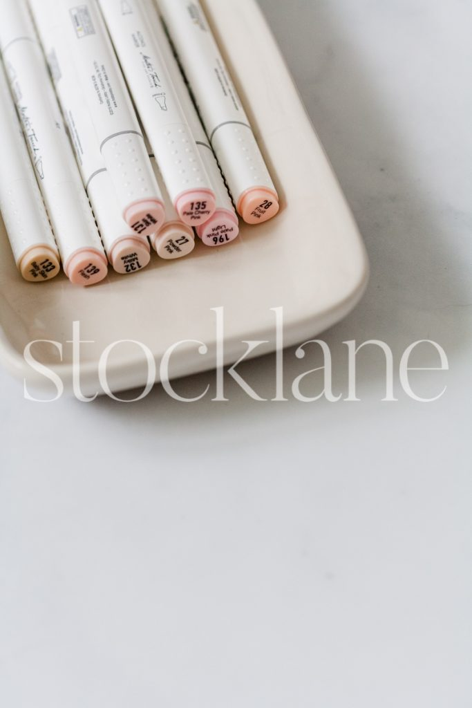 Vertical stock photo of pink toned markers.
