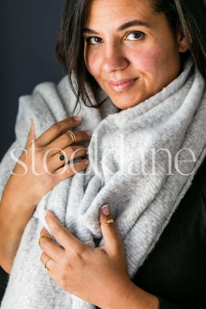Vertical stock photo of woman wearing cozy gray scarf.