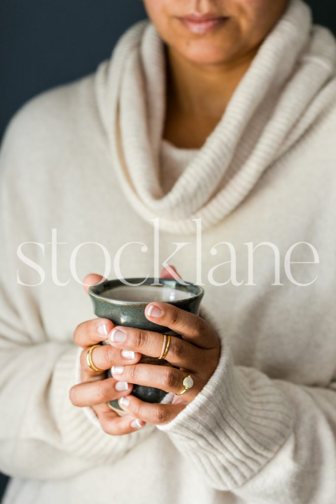 Vertical stock photo of woman holding coffee cup.