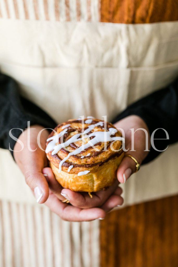 Vertical stock photo of a woman holding a cinnamon roll.