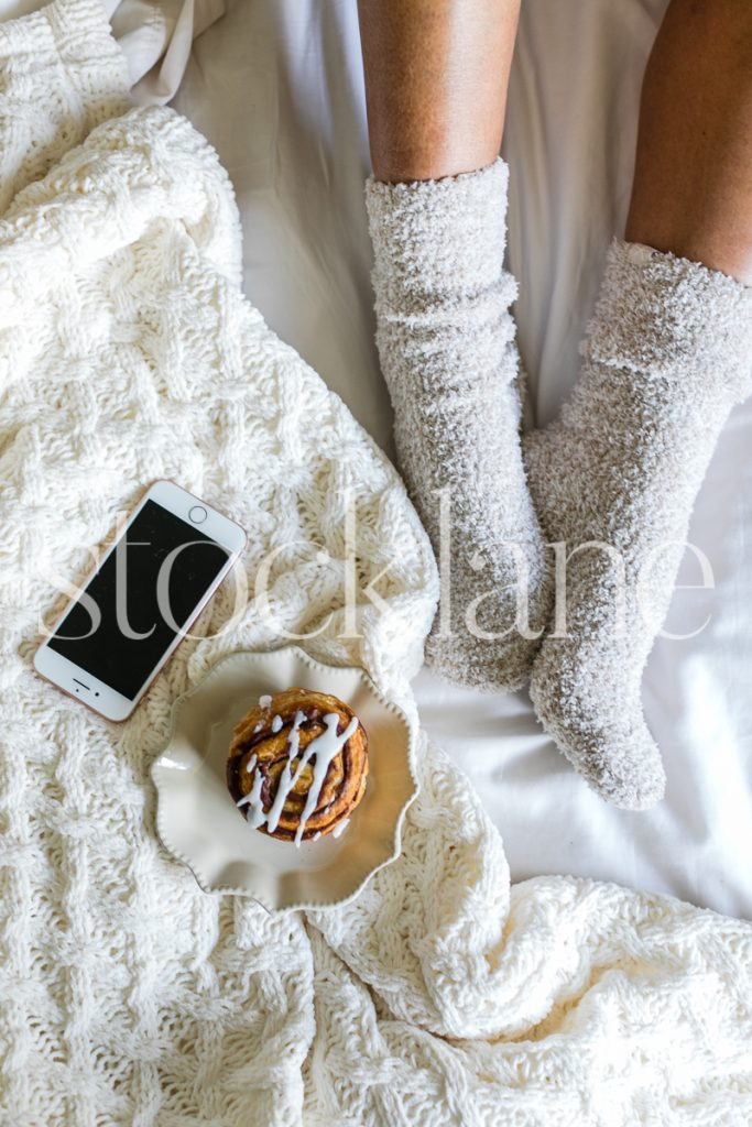 Vertical stock photo of woman in bed with cozy socks and cinnamon roll.