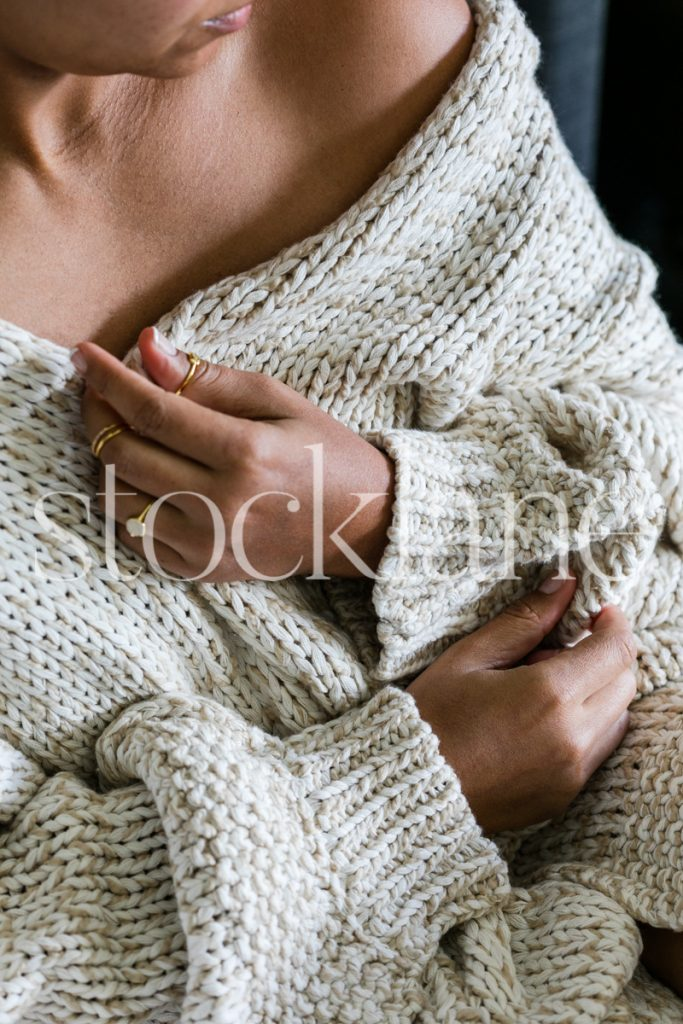 Vertical stock photo of woman wearing cozy sweater.