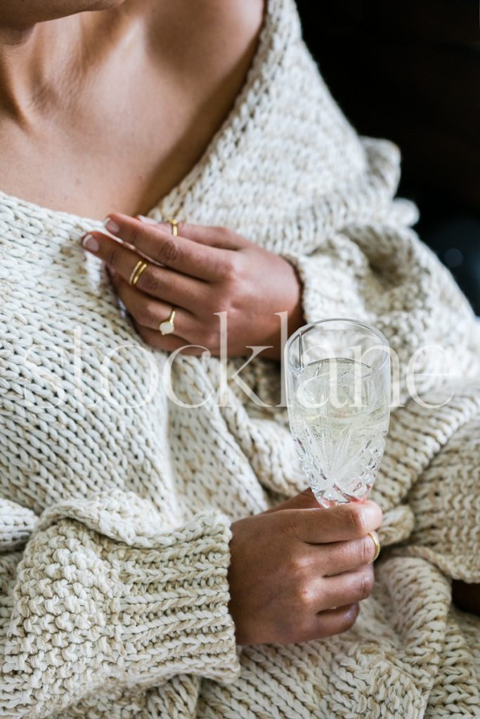 Vertical stock photo of woman wearing cozy sweater and holding a glass of champagne.
