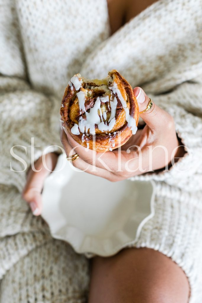 Vertical stock photo of woman eating a cinnamon roll.