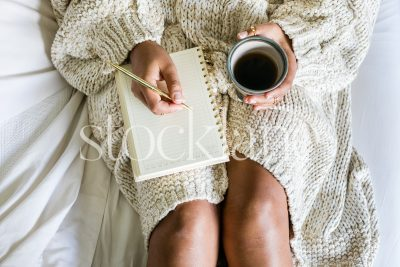 Horizontal stock photo of woman working in bed with coffee and cinnamon roll.