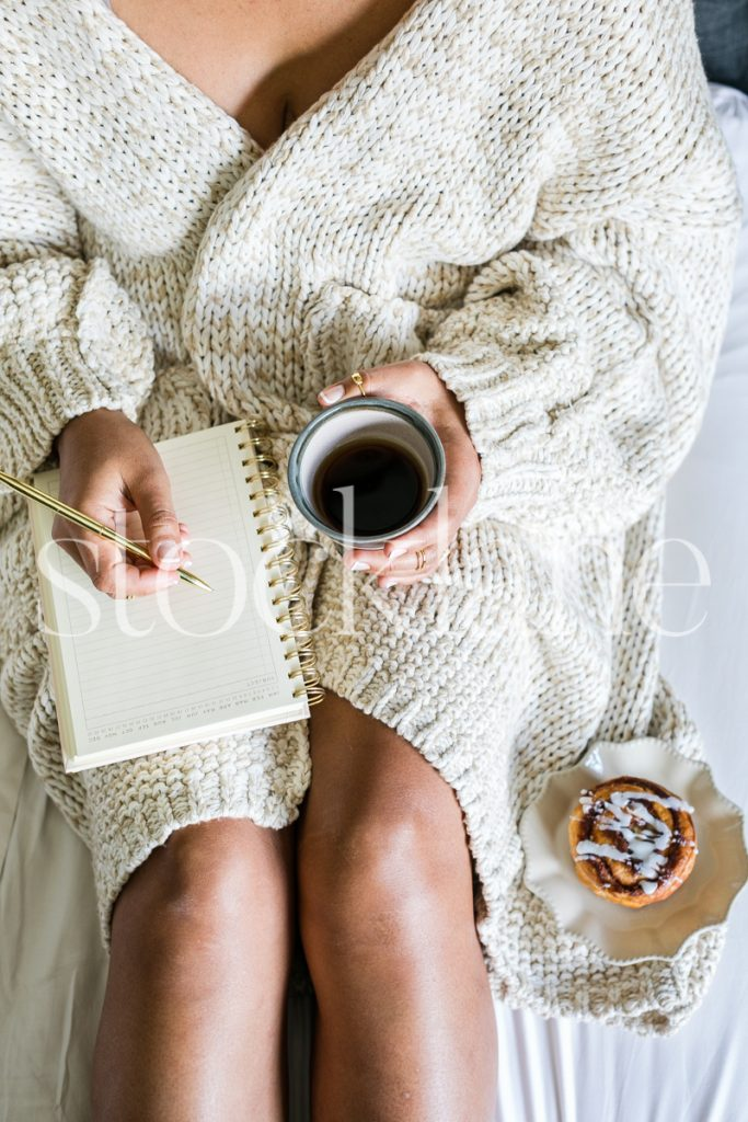 Vertical stock photo of woman working in bed with coffee and cinnamon roll.