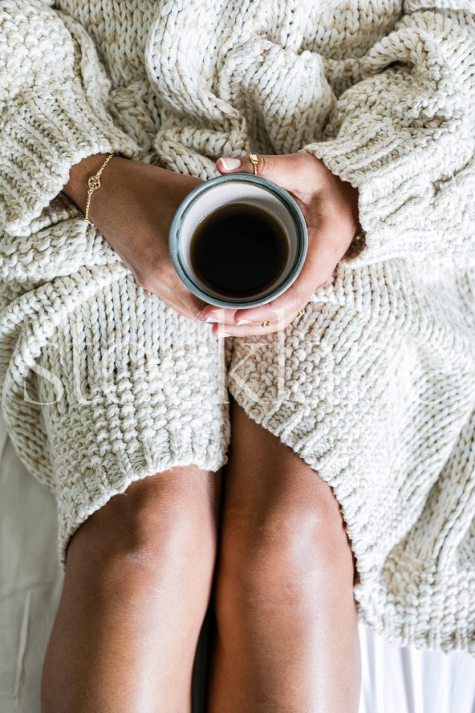 Vertical stock photo of woman holding a cup of coffee.
