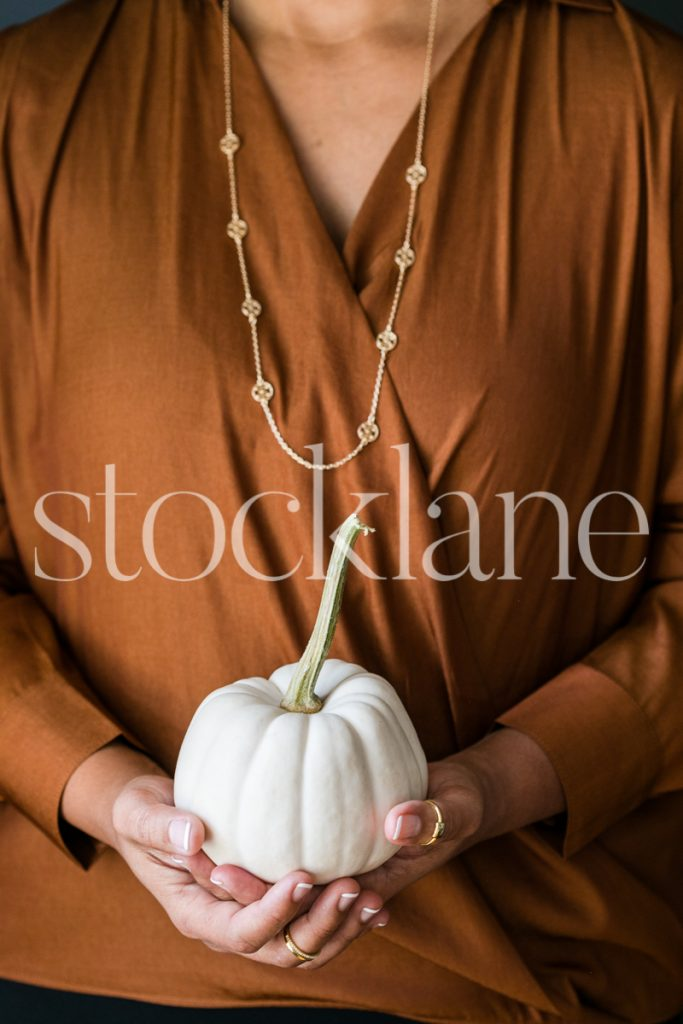Vertical stock photo of a woman holding a white pumpkin.