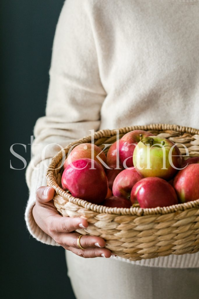 Vertical stock photo of woman holding a basket with apples.