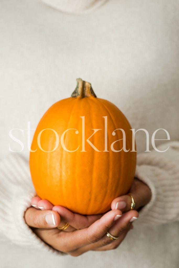 Vertical stock photo of a woman holding a pumpkin.