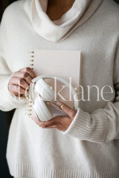 Vertical stock photo of woman holding a notebook and headphones