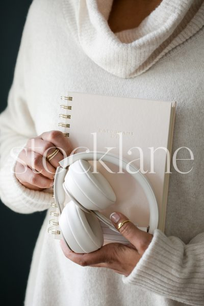Vertical stock photo of woman holding a notebook and headphones.