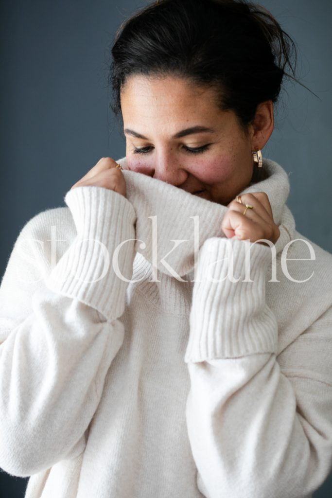 Vertical stock photo of a woman wearing a white sweater.