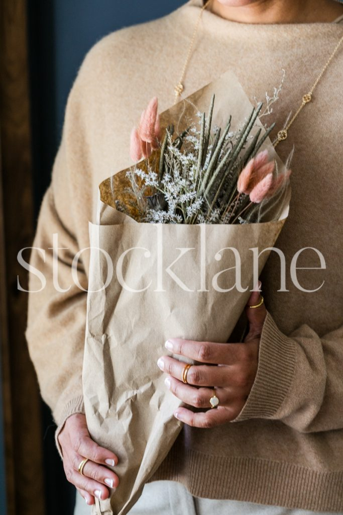 Vertical stock photo of a woman holding a fall bouquet.