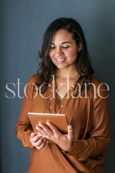 Vertical stock photo of woman holding an iPad.